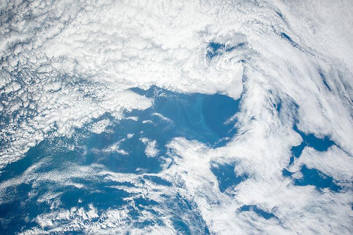Облачные узоры над голубым океаном