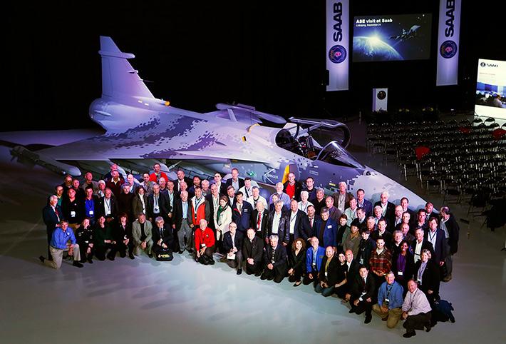 Групповое фото космонавтов и астронавтов 28-го Международного Конгресса Ассоциации Участников Космических Полетов в ангаре фирмы SAAB, г. Линчепинг на фоне самолёта Gripen
